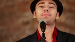 Face of man in black hat and red shirt singing to microphone close-up. Stock Footage