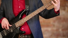 Hands of man in red shirt and jacket playing on bass guitar. Stock Footage