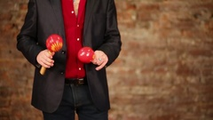 Egg shakers in hand of man in red shirt and black jacket Stock Footage
