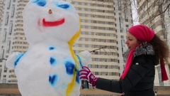 Woman painting snowman with color in aerosol spray can Stock Footage