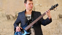 Man in jacket playing on bass guitar and smiling near wall. Stock Footage