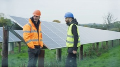 4K Technicians working at solar energy plant, checking the panels & talking Stock Footage