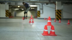 Guy on roller skates jumping diagonally two pile of orange cones Stock Footage