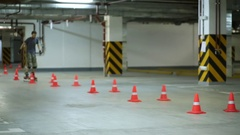 Guy circling lines of orange cones on roller skates on parking. Stock Footage