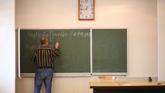 Professor writing formula with white chalk on blackboard in classroom. Stock Footage