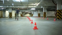Man on roller skates jumping line of cones on underground car parking. Stock Footage
