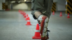 Guy circling line of cones and overthrowing one on one leg on roller skates Stock Footage
