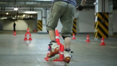 Guy on roller skates breaking two pile of orange cones riding on one leg Stock Footage