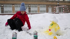 Girl taking in hand aerosol spray can in snow near small snow figure. Stock Footage