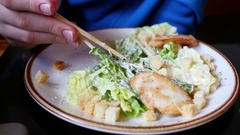 Hand with chopsticks taking leaf of salad Caesar form plate close-up. Stock Footage