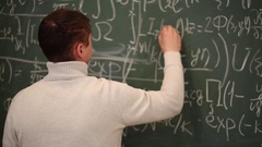 Back of man in sweater correcting symbols in equations on blackboard. Stock Footage