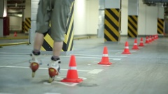 Guy circling cones on one leg on roller skates on underground car parking Stock Footage
