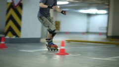 Guy quickly circling orange cones on roller skates on parking. Stock Footage