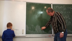 Professor cleaning blackboard and small boy drawing square near. Stock Footage
