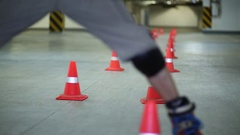 Videographer with action camera shooting man circling cones on roller skates Stock Footage
