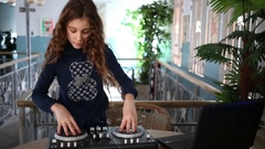 Young girl turning disks at DJ mixer near laptop on table. Stock Footage