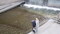 Man with woman  holding hands and standing near artificial waterfall Stock Footage