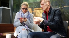 Woman looking in smartphone and man trying to open straw in packet on bench Stock Footage