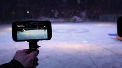 Hand with smartphone shooting robots fighting on arena. Stock Footage