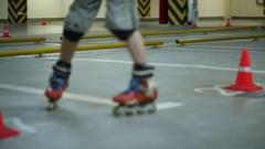 Guy riding backwards circling orange cones eight on roller skates Stock Footage
