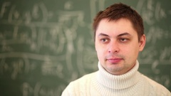 Face of man in sweater close-up turning to blackboard. Stock Footage