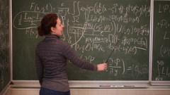 Woman encircle with pointer equations on blackboard, talking Stock Footage