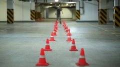 Man accurately circling two lines of orange cones on roller skates Stock Footage