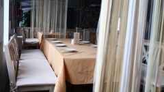 Table with plate and empty chairs near hangings in cafe. Stock Footage