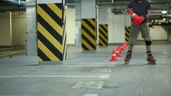 Guy riding on roller skates and placing orange cones in row on parking. Stock Footage