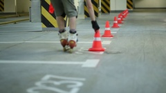 Guy riding on roller skates and collecting to hands orange cones on parking. Stock Footage