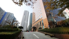 Ground and bushes near highrise building with flag of South Korea Stock Footage