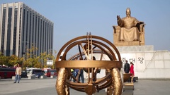 Spherical artwork near big gold monument to King Sejong Stock Footage