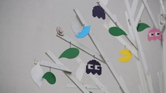 Artificial wood tree with multicolor figures pacman, ghosts and birds Stock Footage