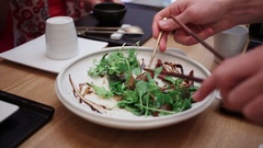 Plate with leaves of salad and hands taking piece with spoon Stock Footage
