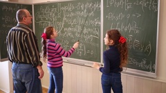 Professor suggesting to girl writing on blackboard with formula near girl Stock Footage
