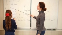 Girl explaining problem solution to woman teacher with pointer Stock Footage
