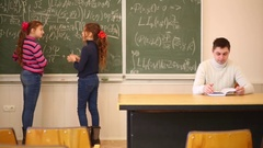 Two girls with pointers disputing near blackboard and man sitting at table Stock Footage