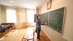Man discussing with woman with pointer equations on blackboard. Stock Footage