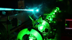 Green laser in optic assembly and bright blue laser above in dark close up. Stock Footage