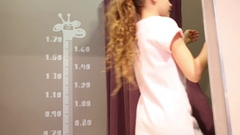 Two young girls dressing and showing in fitting-room in shop. Stock Footage