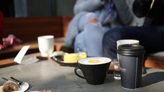 Cups, packets of tea on table (focus on its) and people near in street cafe Stock Footage