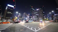 Illuminated cross-road with turning cars and buses among buildings Stock Footage