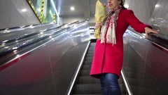 Woman with rose bouquet in hand standing on moving up escalator. Stock Footage