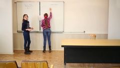 Two girls writing on blackboard inscription classwork, date and variant. Stock Footage