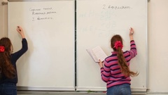Two girls copying to white blackboard conditions of problems. Stock Footage
