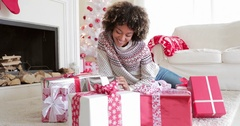 Smiling young woman opening her gifts at Christmas Stock Footage