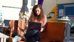 Occupied girl sitting outdoors and browsing internet on laptop Stock Footage