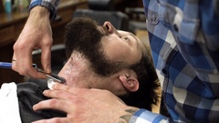 Concentrated Barber shaving beard of client with barber razor Stock Footage
