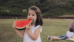 Little girl eating watermelon slice outdoors Stock Footage