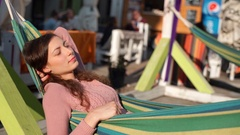 Girl having her eyes closed while lying on comfortable hammock Stock Footage